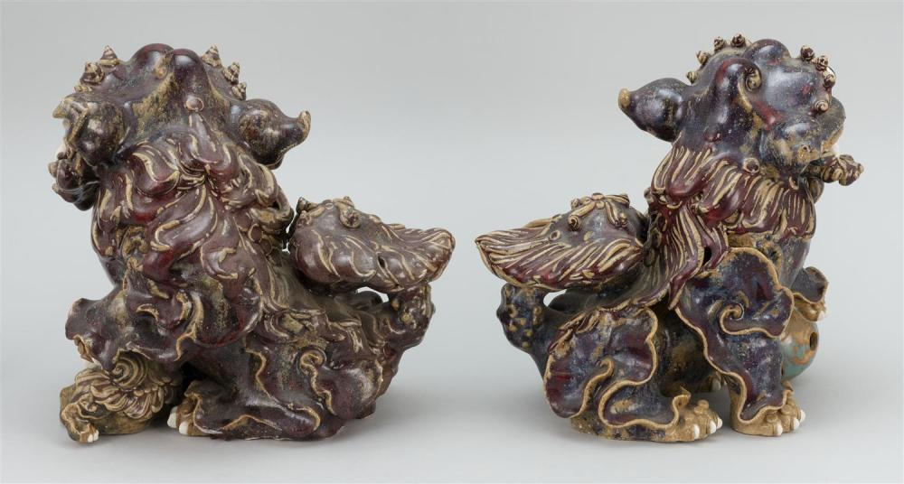 Lot 1016: PAIR OF FLAMBÉ GLAZE POTTERY FU DOG FIGURES One with a pup and the other with a brocade ball. Both with potter's seal marks at tails..