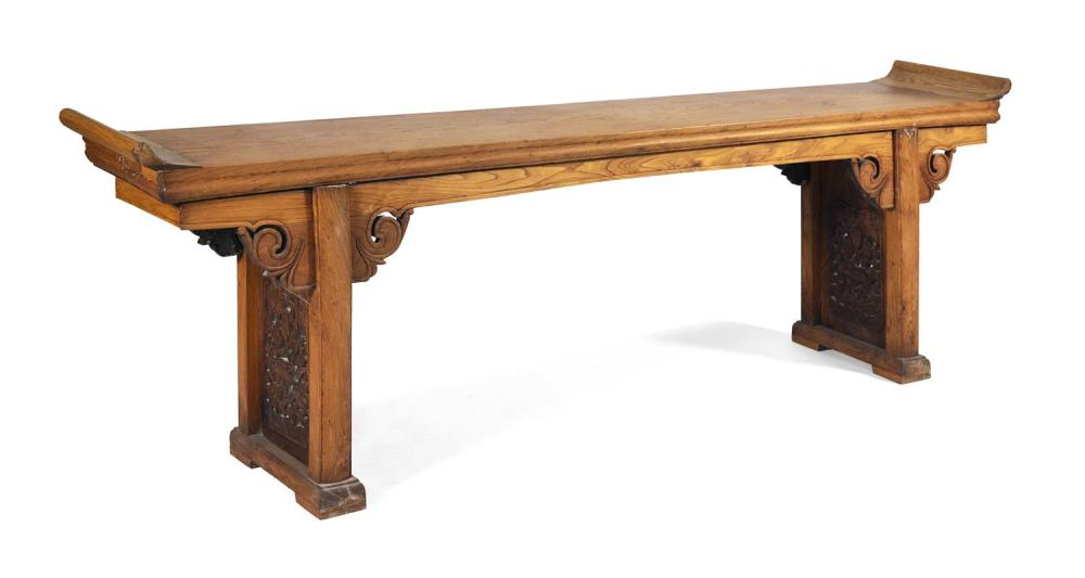 EXCEPTIONALLY LONG ALTAR TABLE Top in huanghuali, with elmwood scrolled ends. Separate base in a darker wood with open carved lotus...