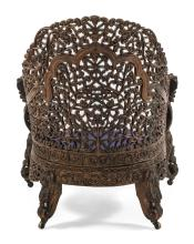 Lot 1040: ANGLO-INDIAN EXTENSIVELY CARVED HARDWOOD ARMCHAIR Foliate and fruit carving throughout. Lion-form heads at end of arms. Back height...