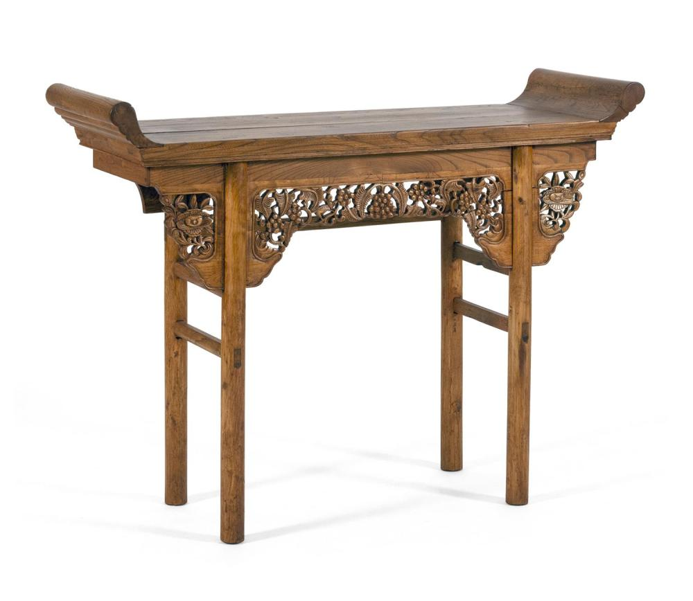 "CHINESE ELMWOOD ALTAR TABLE With carved fruit and foliate apron. Height 37"". Width 47"". Depth 17""."