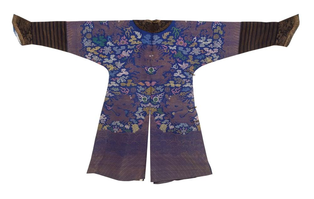 Lot 1141: CHINESE COUNTED STITCH NINE-DRAGON SILK ROBE With polychrome design on blue. Finely detailed horse hoof sleeves. Gilt buttons.