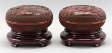 "Lot 1165: PAIR OF DARK RED CINNABAR BOXES Circular, with decoration of figures in a landscape. Black painted interiors. Heights 3.5"". Diameter..."