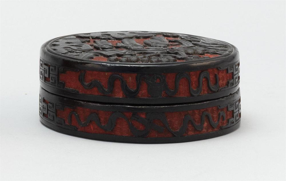 """Lot 1166: CHINESE BLACK AND RED CINNABAR COVERED BOX Circular, with black figural landscape on a red ground. Diameter 5""""."""