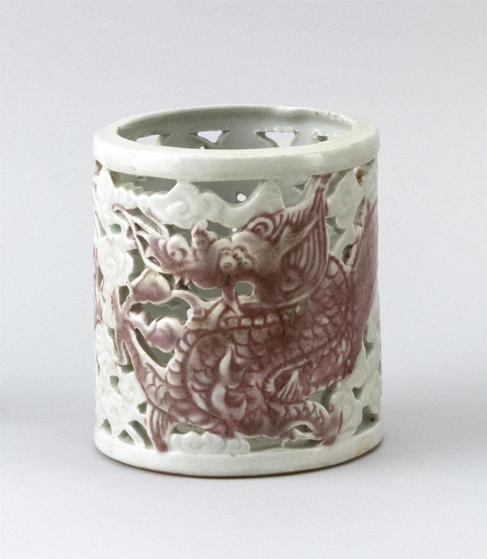 """Lot 1176: KOREAN UNDERGLAZE RED PORCELAIN BRUSH POT Cylindrical, with pierced dragon and cloud design. Height 4.75""""."""