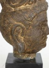 """Lot 1003: STONE HEAD OF BUDDHA Wearing a pearl-decorated crown. Height 10"""". Ex Collection: Sackler Museum."""