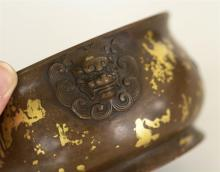 Lot 927: CHINESE SUNSPOT BRONZE CENSER In squat ovoid form, applied mask handles and gilt splashes on a bronze ground. Four-character Xuande...
