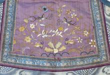 "Lot 1146: CHINESE SILK NEEDLEWORK CHILD'S BIB With forbidden stitch bird and flower design on a purple ground with ruyi border. Length 14.5""."