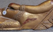 Lot 925: TIBETAN GILTWOOD FIGURE OF RECLINING BUDDHA With traces of red paint. Headdress and robes lined in green and mirrored cabochons. Hei...