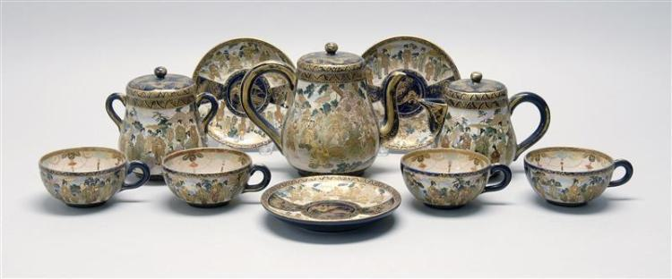 SATSUMA POTTERY TEA SET A teapot, creamer, sugar, four cups and three saucers in cobalt blue with decoration of samurai in a landsca...