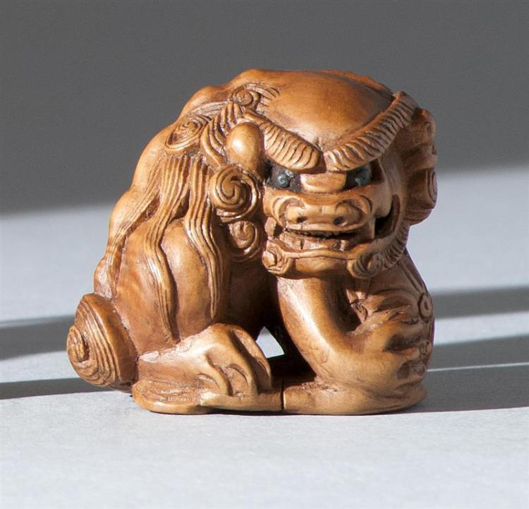 """WOOD NETSUKE In the form of a guardian lion holding a brocade ball. Stained eyes. Signed. Height 1.5"""" (3.7 cm)."""