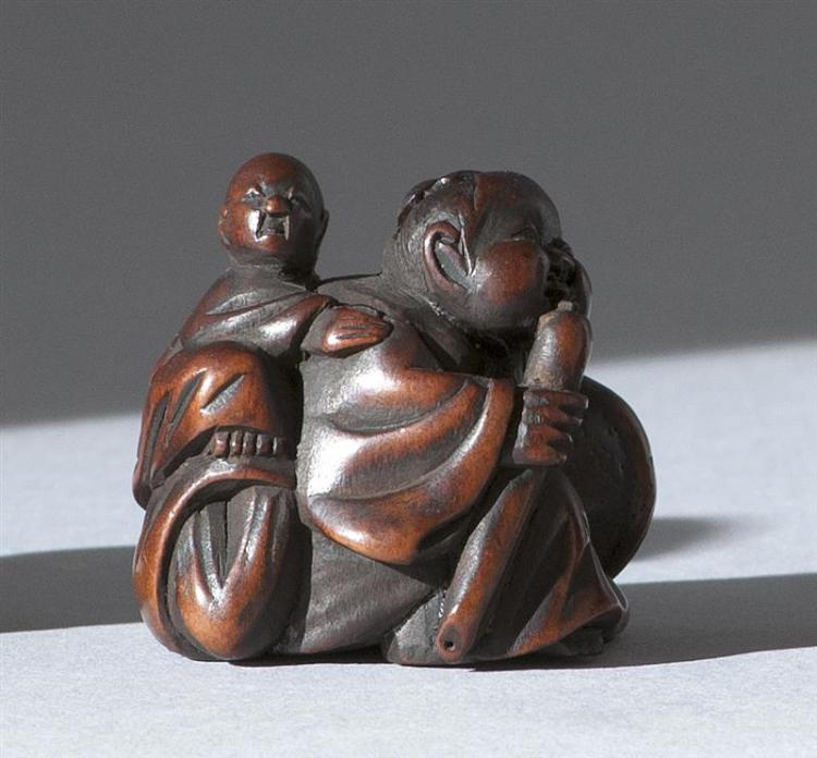 """WOOD NETSUKE By Hidekazu. Depicting a child climbing on the back of Okame. Signed. Height 1.2"""" (3 cm)."""