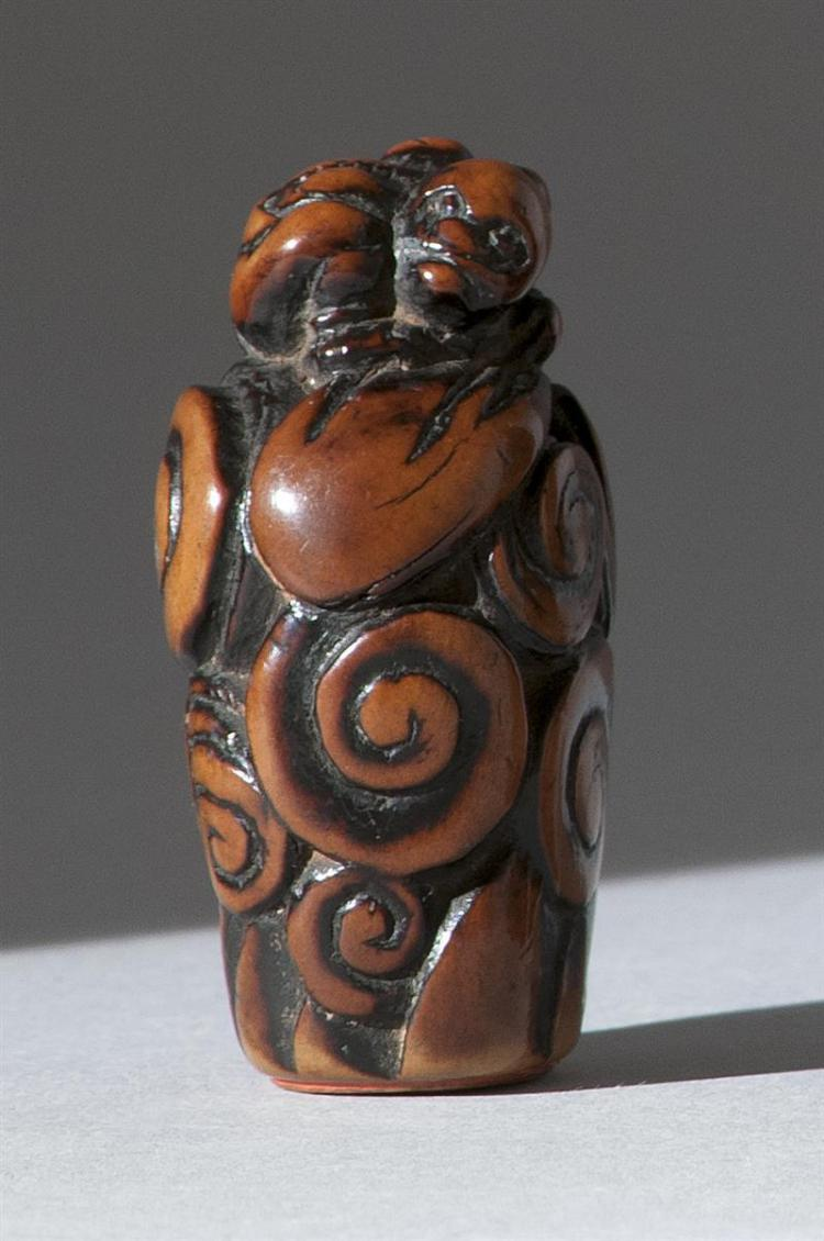 """WOOD SEAL-TYPE NETSUKE In the form of Raiden with his thunder sack lying atop swirling clouds. Seal-cut base. Height 2"""" (5 cm)."""