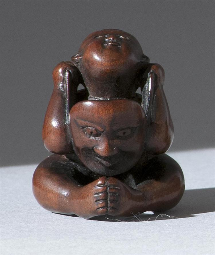 """WOOD NETSUKE By Rakumin. Depicting a boy with inlaid eyes putting on a theatrical mask. Signed. Height 1.3"""" (3.5 cm)."""
