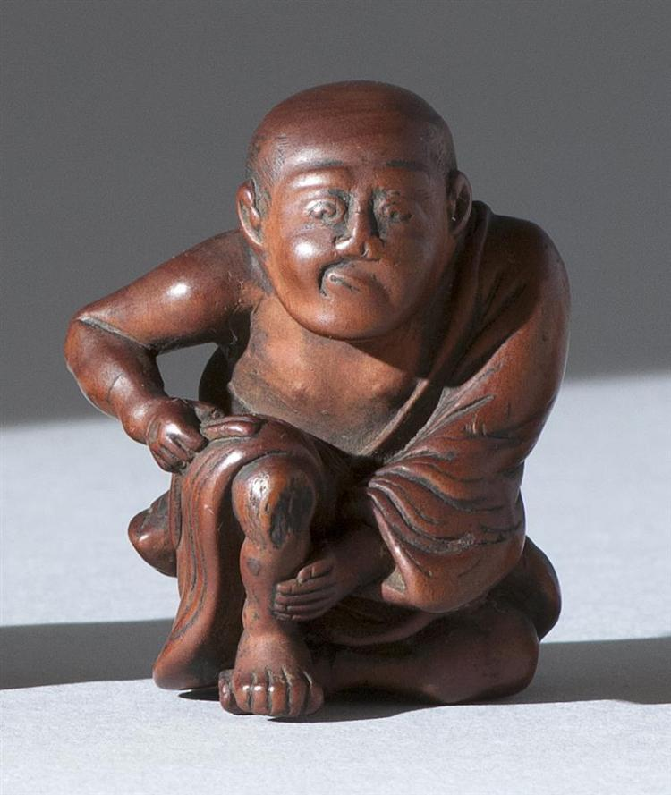 "WOOD NETSUKE Depicting a man studying an abrasion on his knee. Height 1.8"" (4.6 cm)."