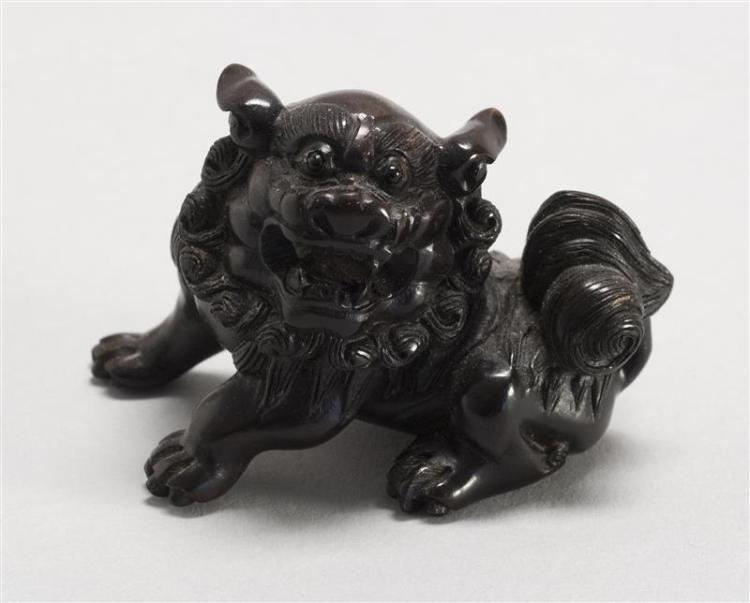 """WOOD NETSUKE In the form of a fierce lion with inlaid eyes. Signed. Length 2.25"""" (5.8 cm)."""