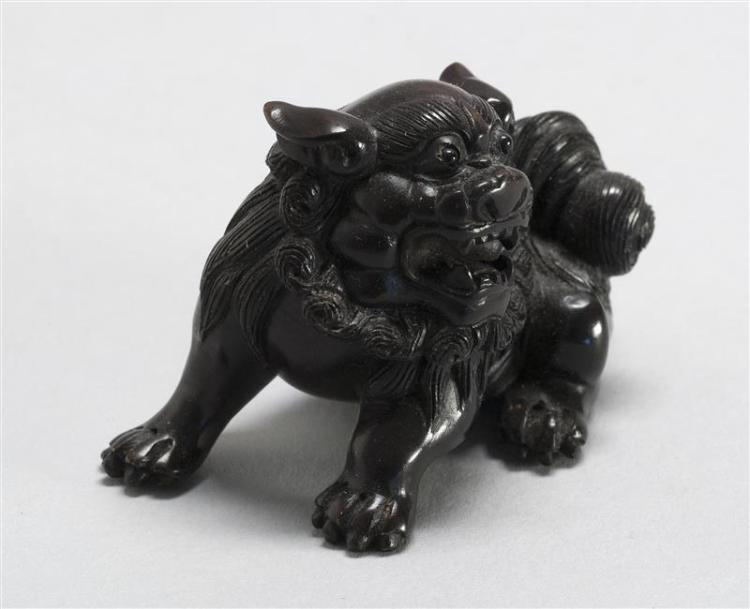 WOOD NETSUKE In the form of a fierce lion with inlaid eyes. Signed. Length 2.25