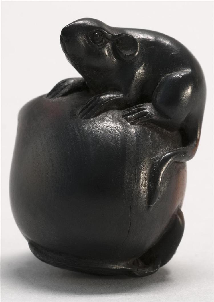 """EBONIZED WOOD NETSUKE In the form of a rat resting on a large peach. Height 1.6"""" (4.2 cm)."""