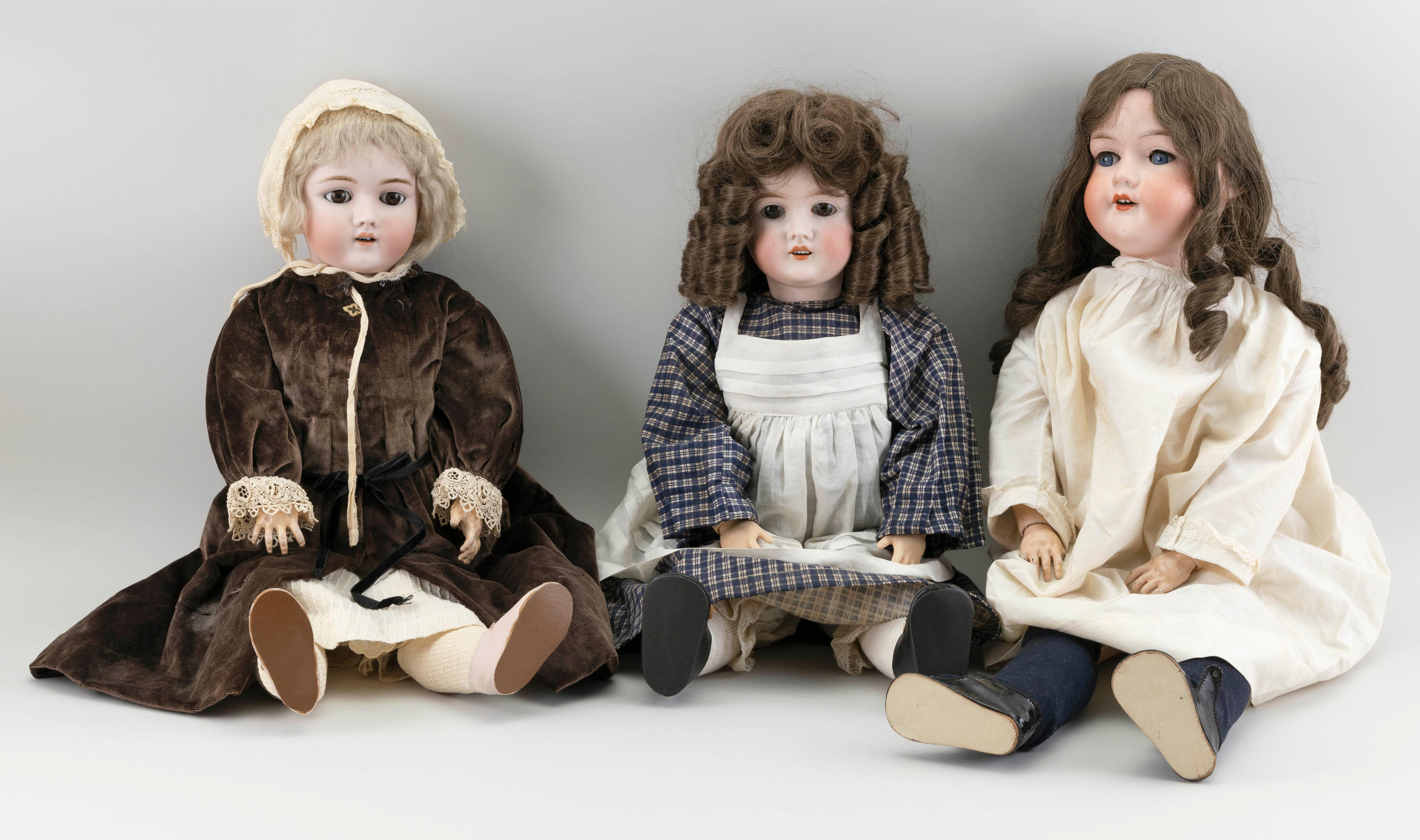 """THREE GERMAN BISQUE-HEAD DOLLS Circa 1910 Heights from 21"""" to 28""""."""