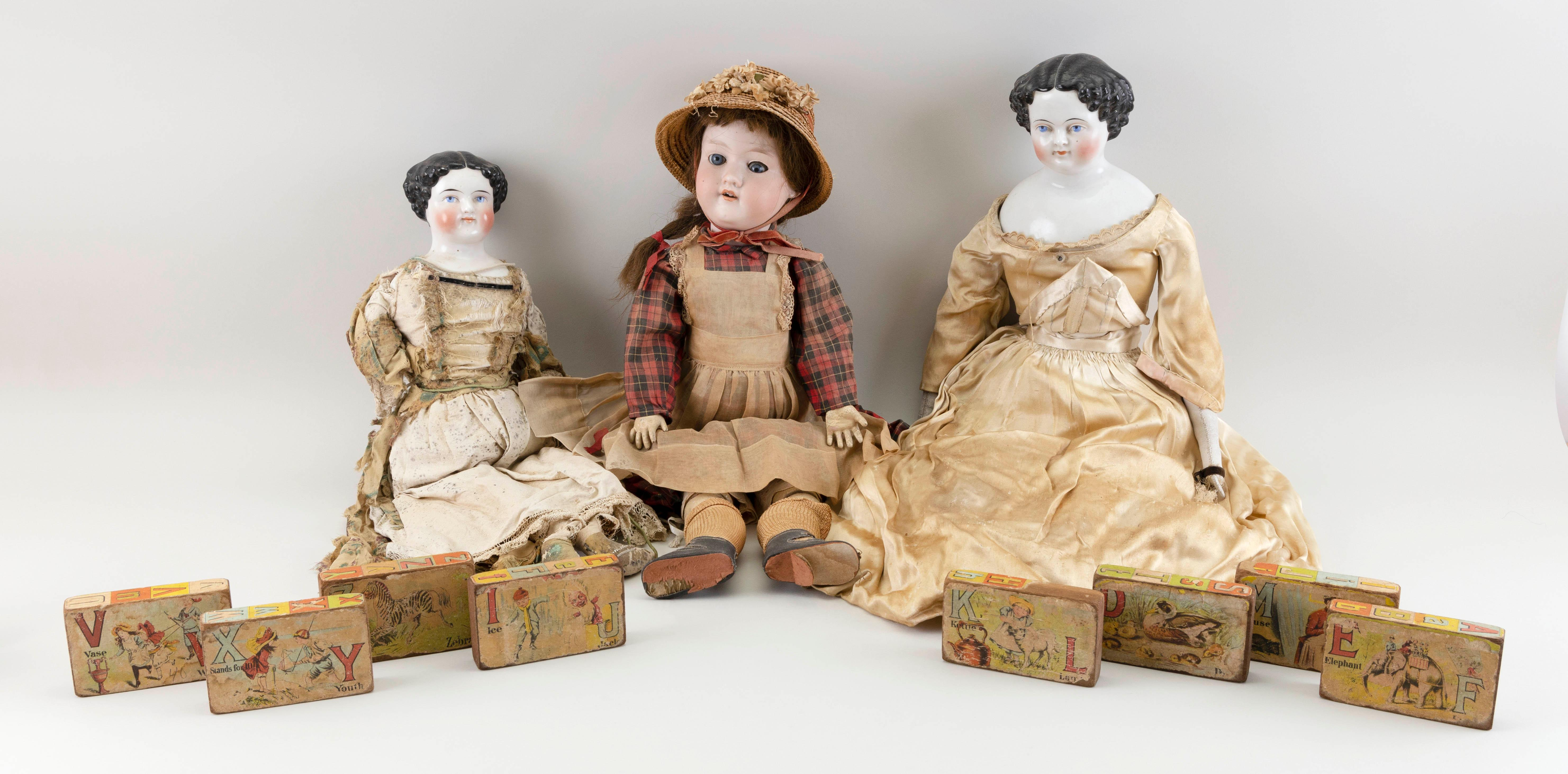 "THREE GERMAN DOLLS AND EIGHT LITHOGRAPHED WOODEN BLOCKS Circa 1910 Doll heights from 18"" to 22"". Blocks heights 4""."