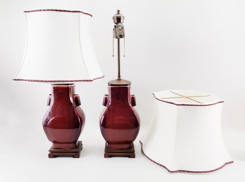 "PAIR OF SANG DE BOEUF FLAMBÉ PORCELAIN HU-FORM VASES Vase heights 12"". Total heights 27""."