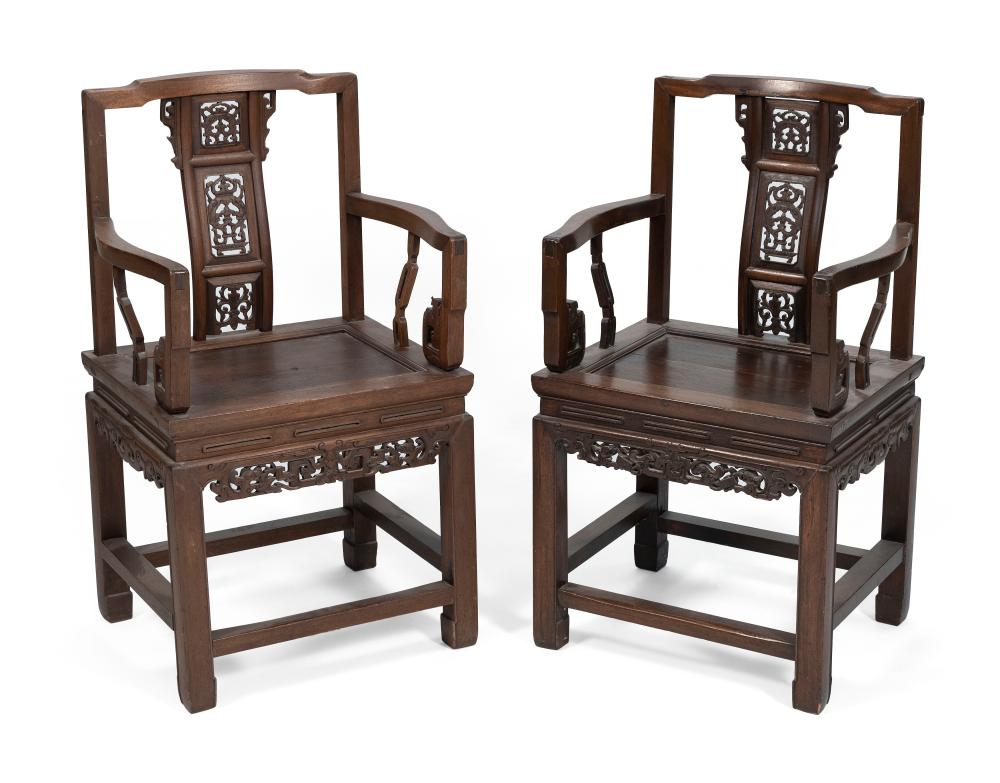 """PAIR OF CHINESE CARVED ELMWOOD ARMCHAIRS Early 20th Century Back heights 40"""". Seat heights 21"""". Widths across arms 21""""."""