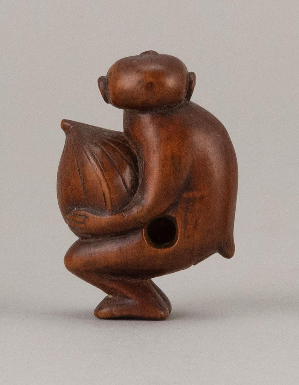 JAPANESE WOOD NETSUKE In the form of a monkey carrying a large chestnut. Height 2