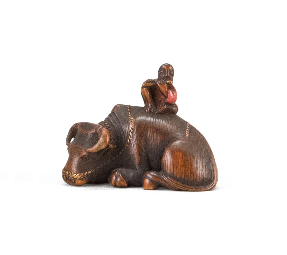 "JAPANESE WOOD NETSUKE In the form of a herd boy seated on a reclining water buffalo. Some lacquer highlights. Length 1.5""."