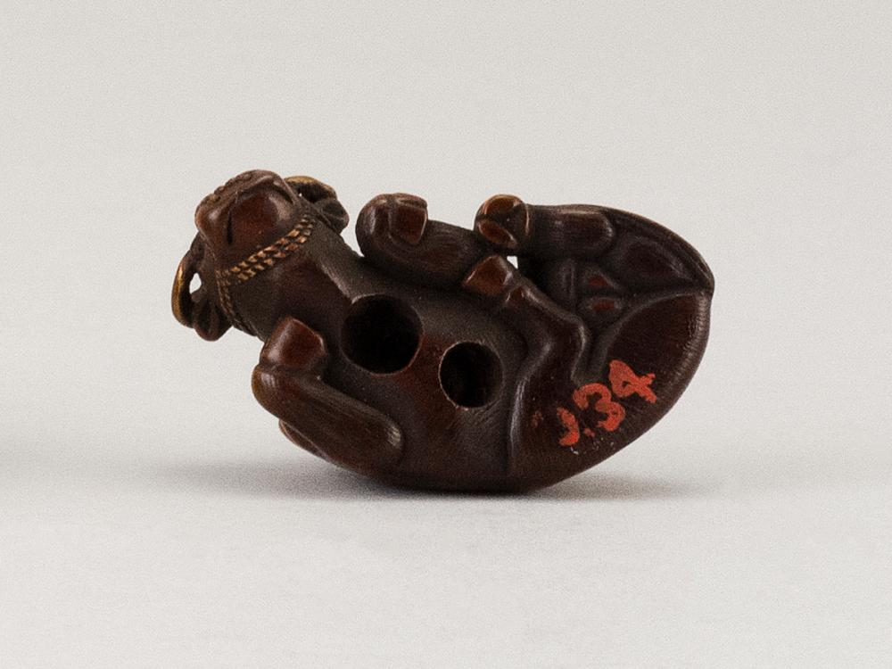 JAPANESE WOOD NETSUKE In the form of a herd boy seated on a reclining water buffalo. Some lacquer highlights. Length 1.5