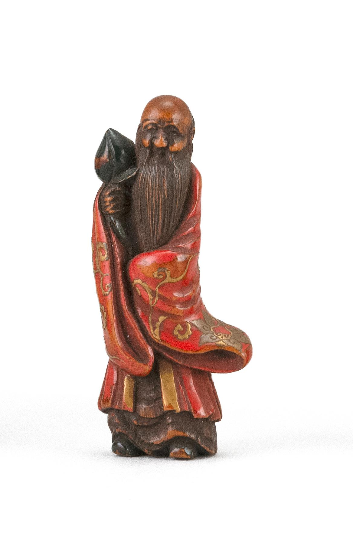 JAPANESE GOLD, RED AND GREEN LACQUER-ON-WOOD NETSUKE In the form of a standing sage dressed in a passionflower-decorated robe and ho...