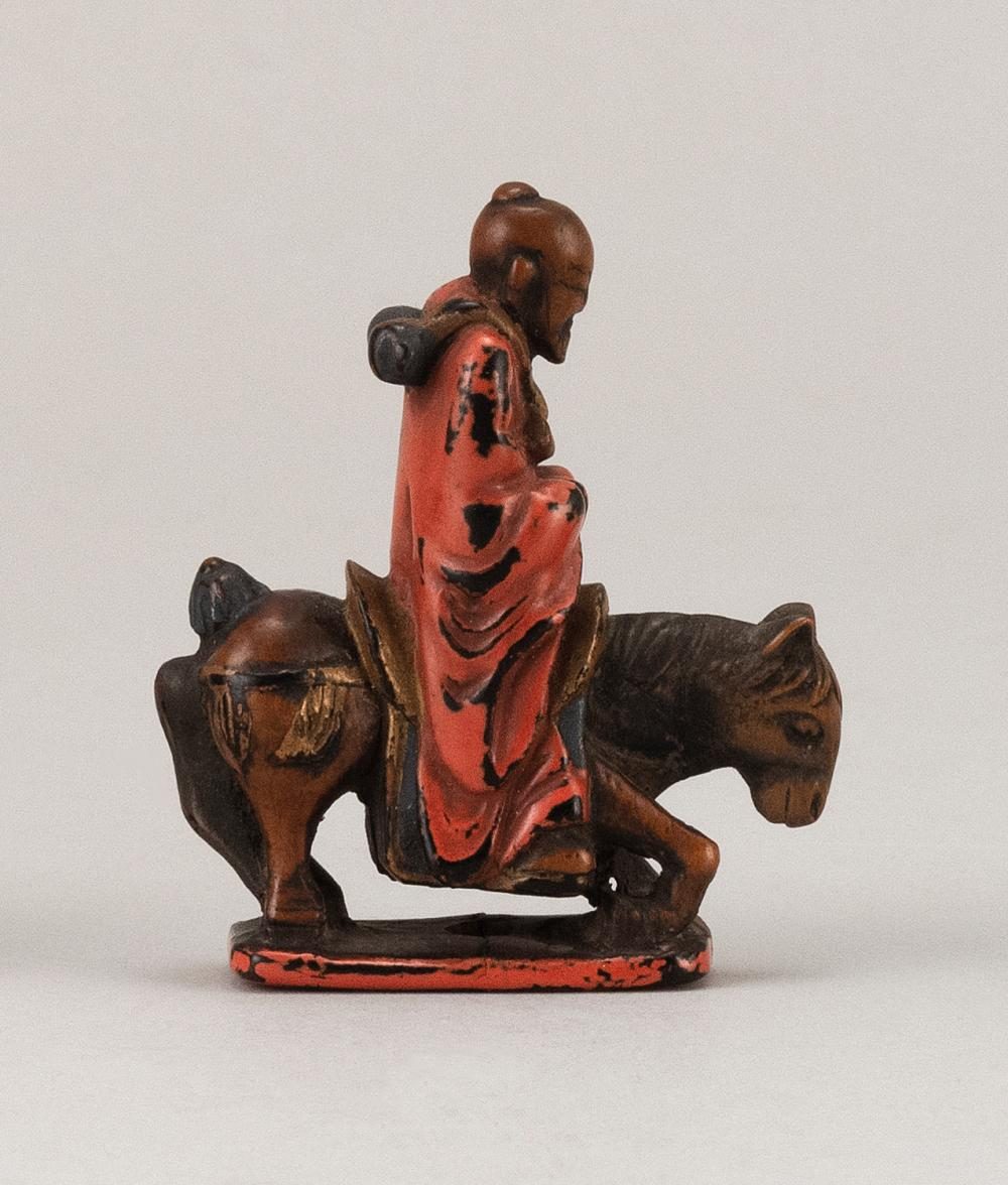 JAPANESE NEGORO LACQUER-ON-WOOD NETSUKE In the form of a scholar riding a horse. Set on a rectangular base. Height 2