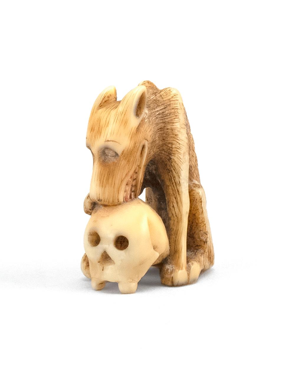 "JAPANESE BONE NETSUKE In the form of a wolf with a decaying human skull. Height 1.6""."