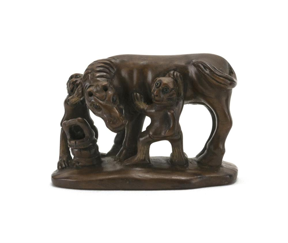 """JAPANESE WOOD NETSUKE In the form of a horse being groomed by two monkeys. Signed. Length 2""""."""