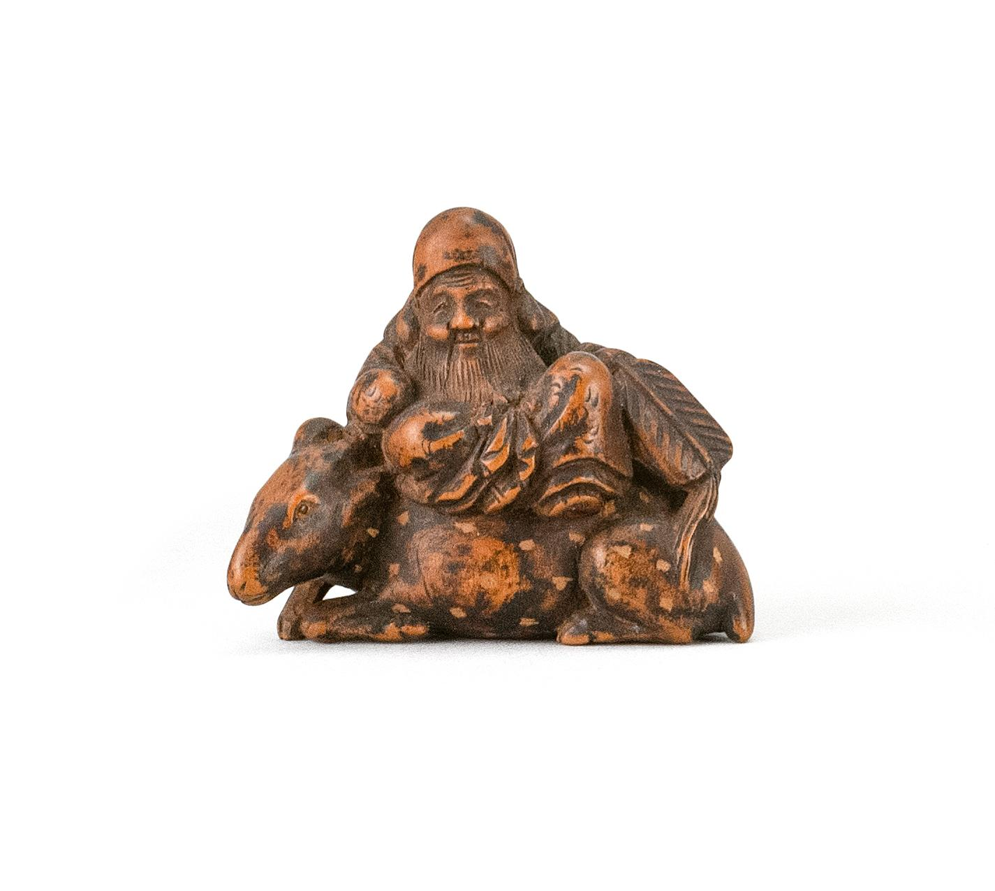 """JAPANESE WOOD NETSUKE By Isshinsai Masatoshi. In the form of Jurojin seated on a deer while holding a child. Signed. Length 1.5""""."""