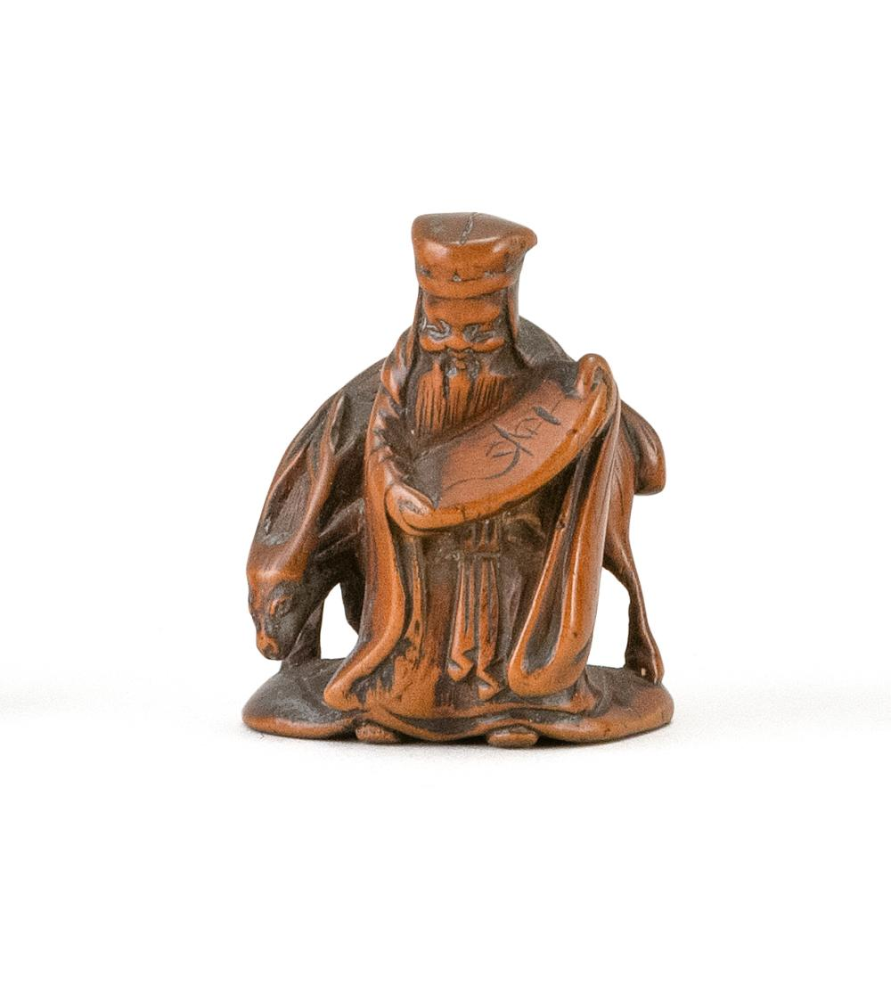 JAPANESE WOOD NETSUKE By Jugyoku. In the form of Jurojin with an open scroll standing beside a deer. Signed on inlaid plaque. Height...