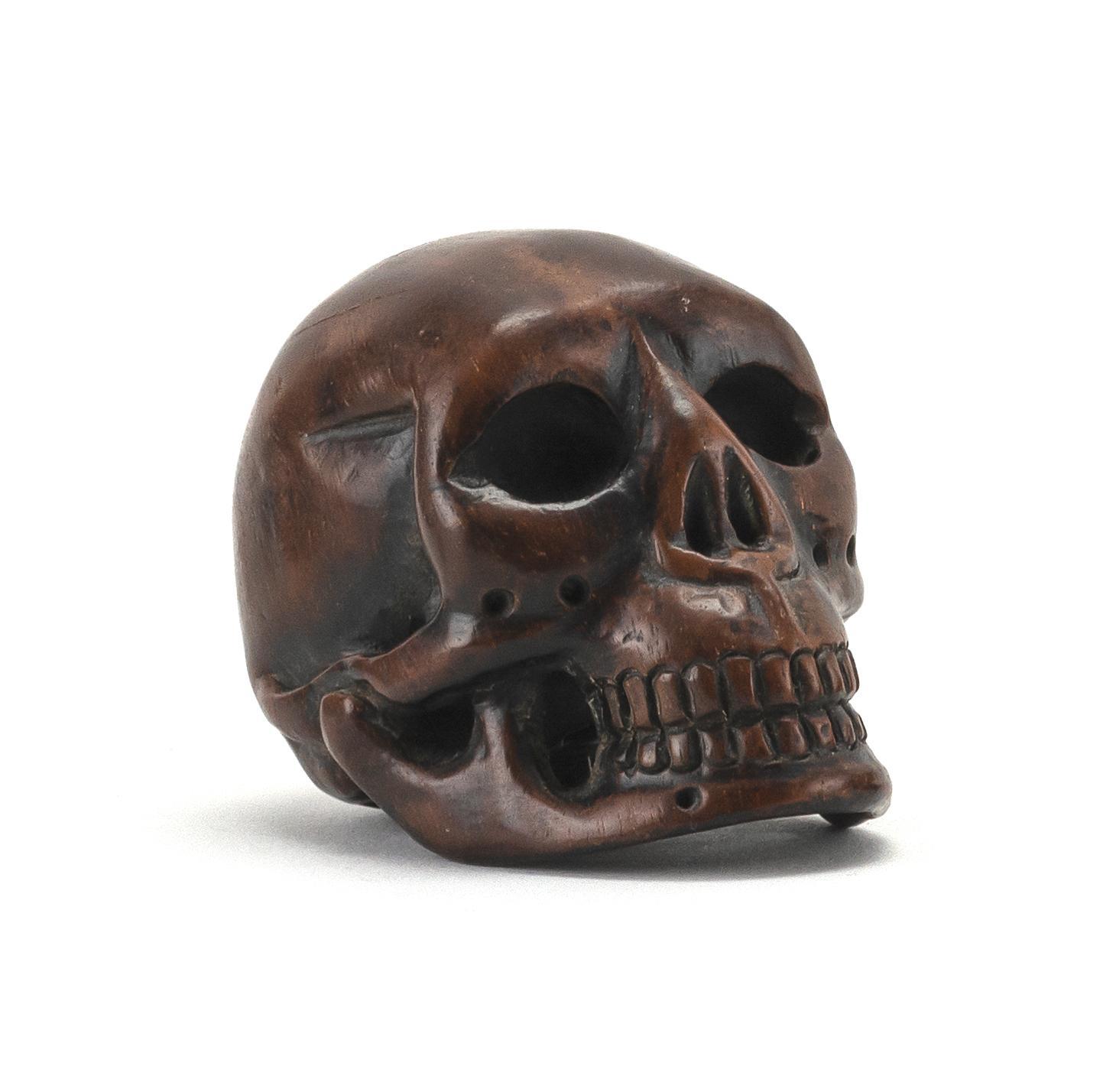 "JAPANESE WOOD NETSUKE In the form of a skull. Length 2""."