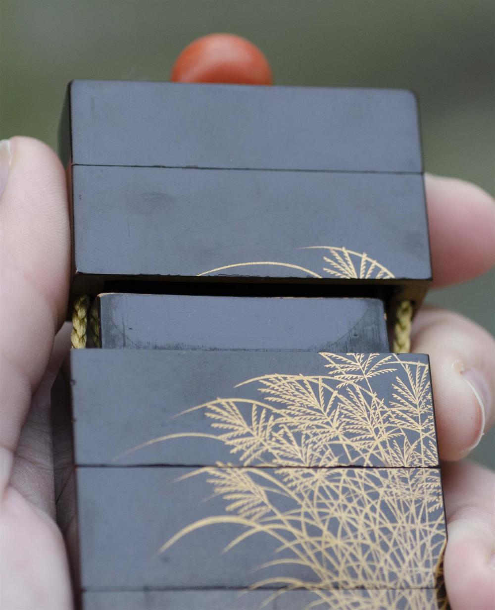JAPANESE BLACK AND GOLD LACQUER FOUR-CASE INRO Rectangular, with grasses design. Signed. Length 3.5