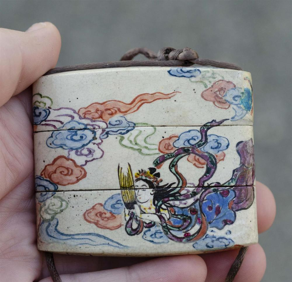 JAPANESE CERAMIC TWO-CASE INRO Signed Kenzan. Decorated with a polychrome scene of an apsara in clouds playing a shou. Length 2.25