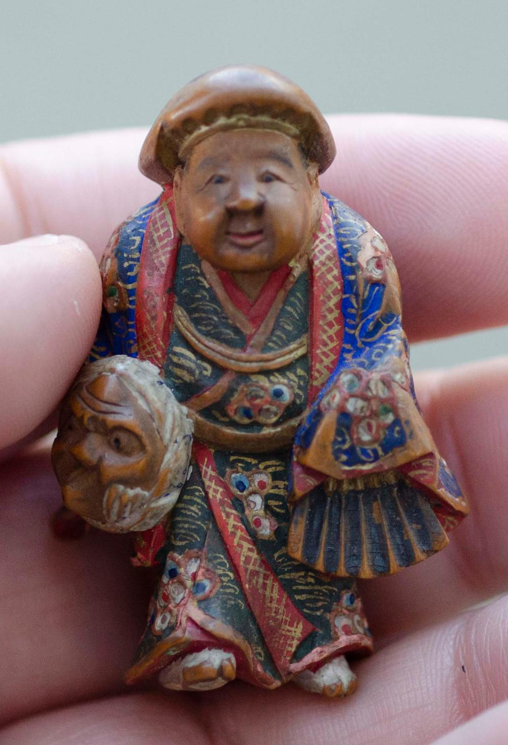 JAPANESE POLYCHROME WOOD NETSUKE By Nagamachi Shuzan. In the form of a figure carrying a mask and folded fan. Signed. Height 1.75