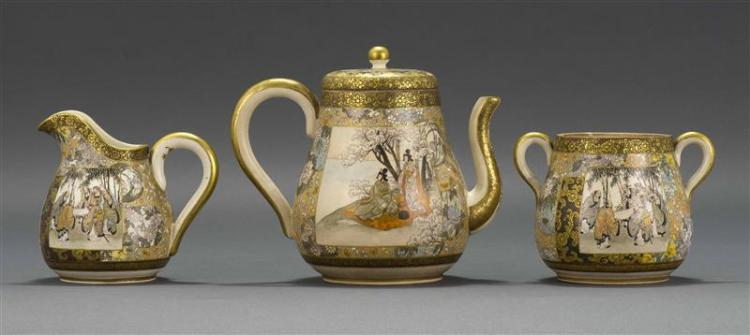 THREE-PIECE SATSUMA POTTERY TEA SET Includes pear-shaped teapot, creamer, and sugar bowl. Decorated with scholars in a bamboo grove...