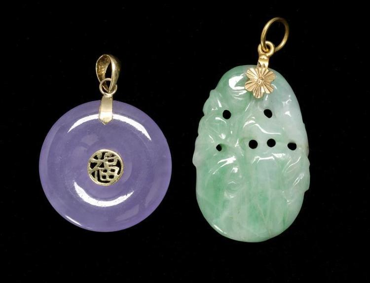 TWO JADE PENDANTS One in green in a fruit design, length 2.5 cm, and the other in lavender in a circular design. Diameter 2.0 cm.