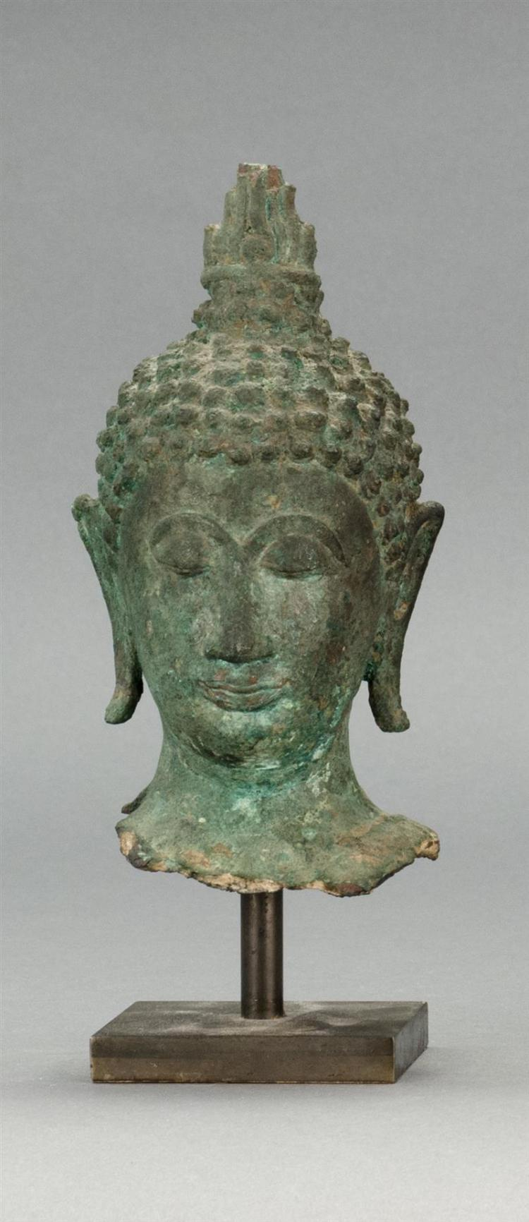 BRONZE HEAD OF BUDDHA With tightly curled hair knots, top knot, and elongated earlobes. In a green patina. Height 6.5
