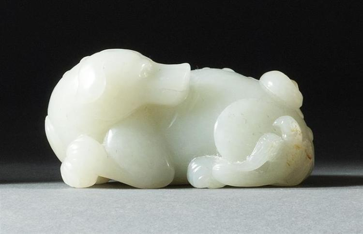 WHITE AND RUSSET JADE CARVING In the form of a reclining dog with an eagle. Length 3.25