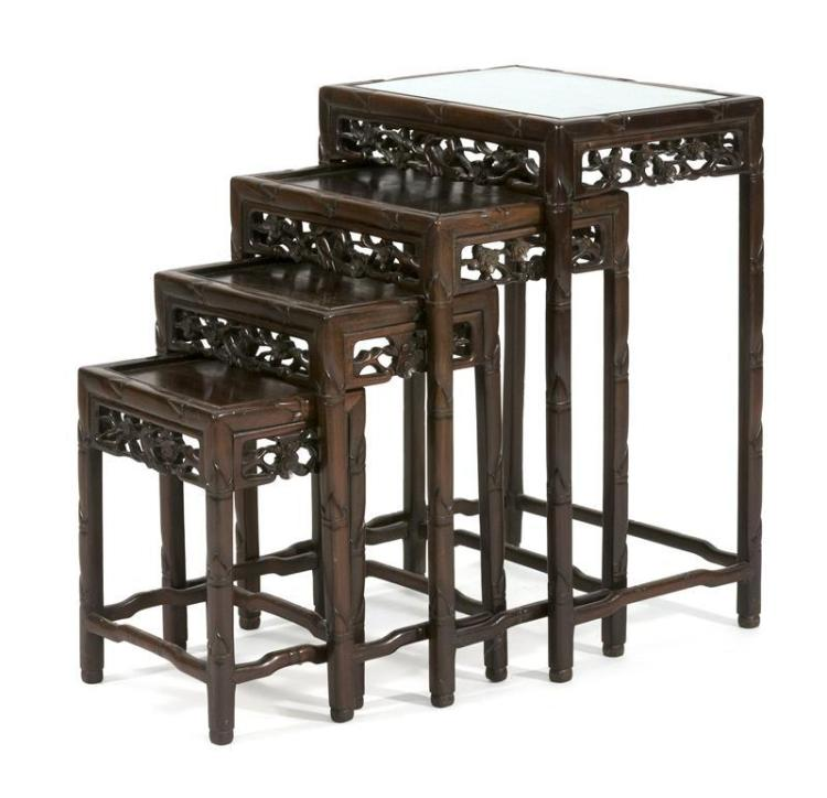 NEST OF FOUR ROSEWOOD TABLES With openwork prunus and bird carving and bamboo-carved legs. Largest with glass top. Heights 16