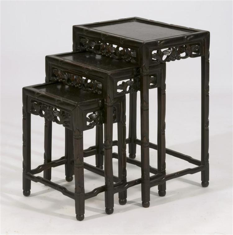 THREE ROSEWOOD NESTING TABLES With openwork lotus and berry carving on aprons. Heights 16