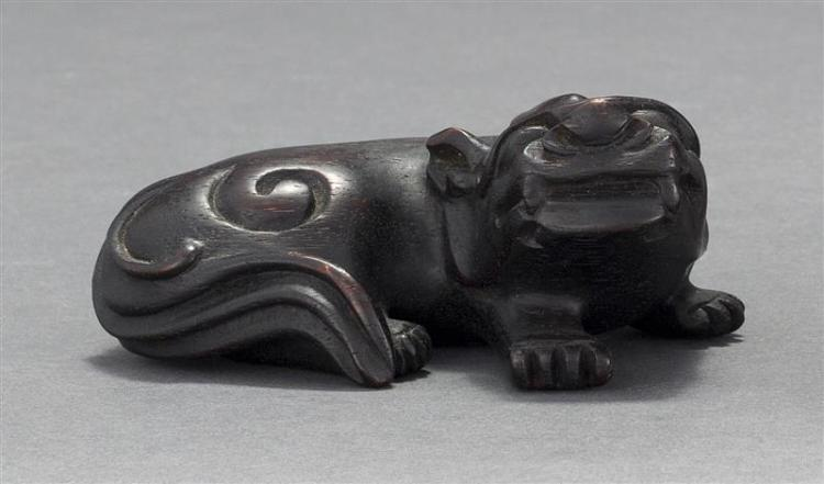 CARVED WOOD FIGURE OF A QILIN In a crouched position with turned head. Length 4