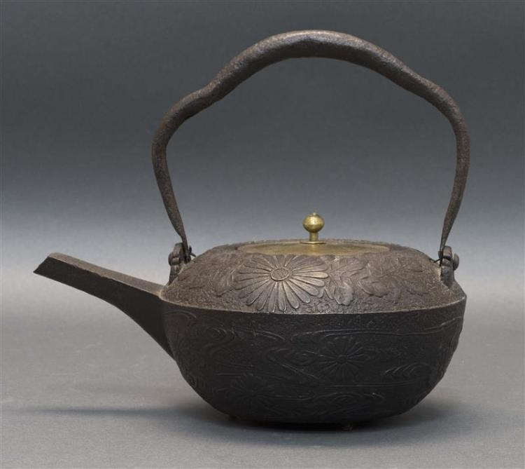 CAST IRON TETSUBIN In squat ovoid form with raised chrysanthemum decoration. Swing handle. Length 9