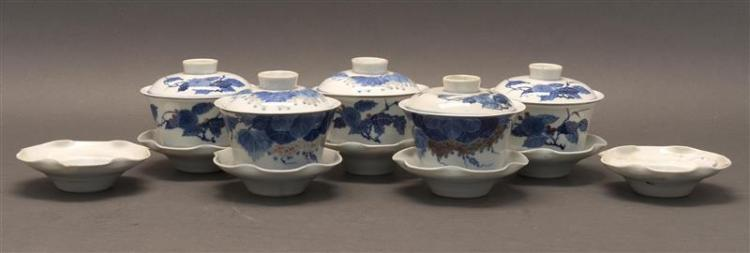 FIVE BLUE AND WHITE PORCELAIN COVERED CUPS AND UNDERTRAYS With flower and grape designs. Diameters 4.2
