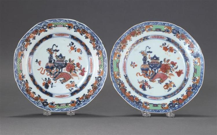 TWO POLYCHROME PORCELAIN PLATES With nearly matching central garden urn and vase decoration surrounded by floral and foliate design....