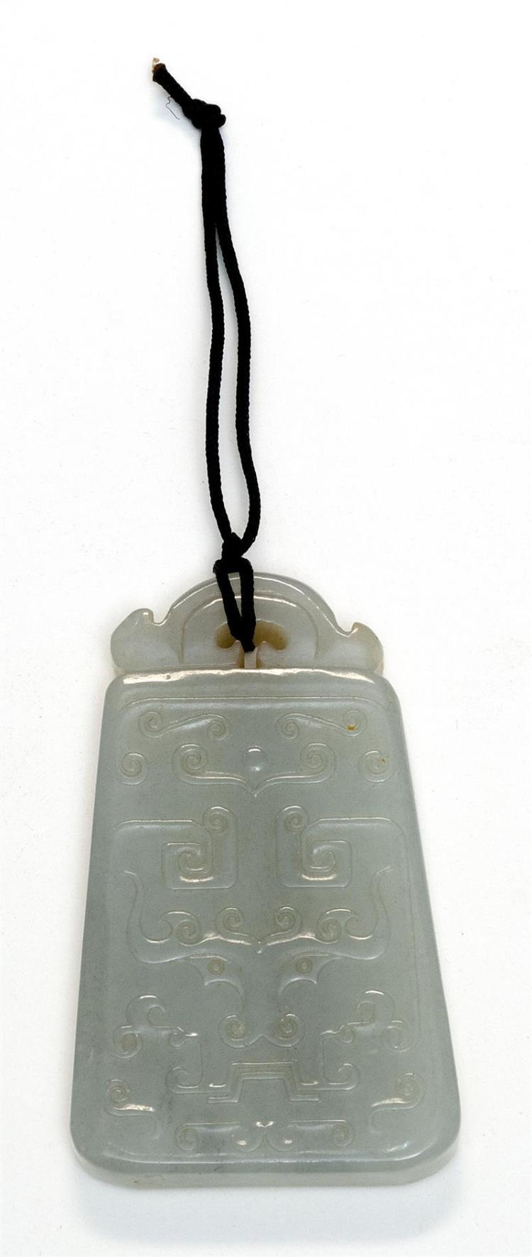 WHITE JADE PENDANT In bell form with mask carving. Length 2.5