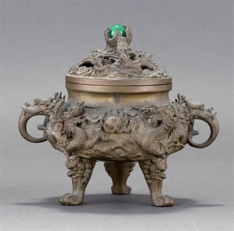 BRONZE CENSER In ovoid form. With three mask-design feet and high-relief dragon decoration. Pierced cover with glass ball finial. Si...